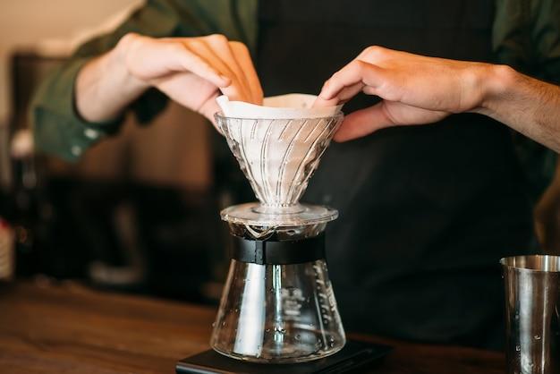 Close-up van mannelijke handen bereidt koffiepot staande op toog.