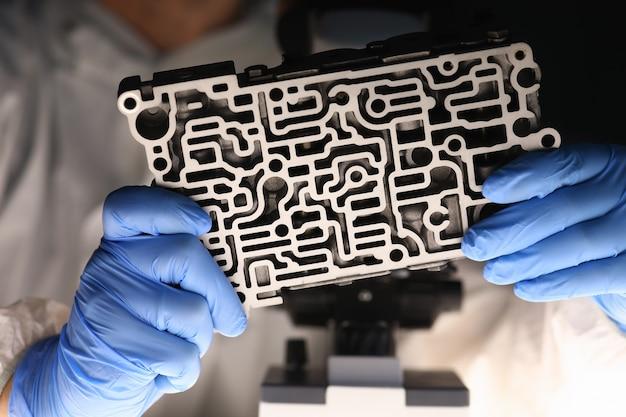 Close-up van mannelijke handen die automatisch transmissiedetail houden. automonteur metalen slushbox hydraulische controle labyrint controleren. transport technologie concept