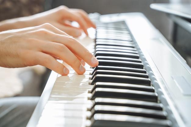 Close-up van mannelijke handen die de elektrische piano spelen.