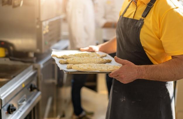 Close-up van mannelijke handen die een dienblad met khachapuri houden, die naar de oven voorbereidingen treffen te verzenden. traditioneel georgisch kaasbrood. georgisch eten.