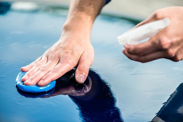 Close-up van mannelijke handen die het oppervlak van een blauwe auto in de was zetten bij autowas