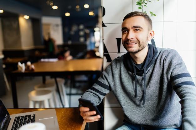 Close-up van mannelijke handen die moderne slimme telefoon in koffiewinkel houden en gebruiken.