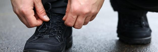 Close-up van mannelijke handen die op straat gaan zitten en schoenveters op tennisschoenen binden. persoon die modieuze sportschoenen rijgt. sport, wandelen en hardlopen concept