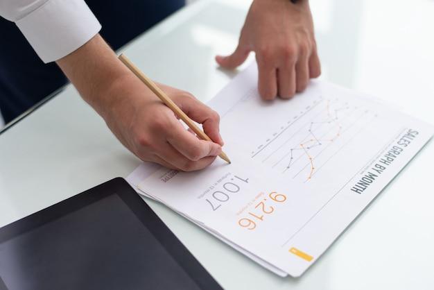 Close-up van mannelijke handen die op verkooprapport schrijven in bureau