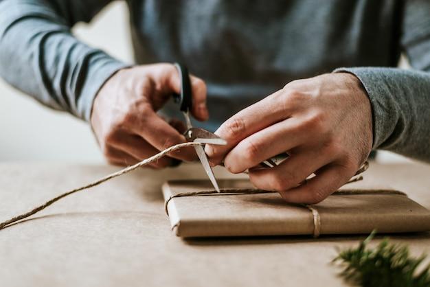 Close-up van mannelijke handen inwikkeling aanwezig met natuurlijke touw en ambachtelijke papier.