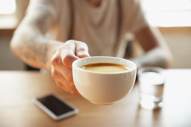 Close up van mannelijke handen kopje koffie voorstellen, zittend aan de tafel met smartphone. surfen, online winkelen, werken. onderwijs, freelance, kunst en business concept. drinken. warme aromadrank.