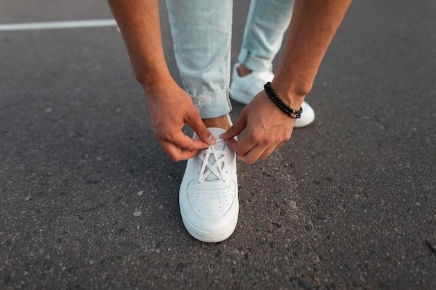 Close-up van mannelijke handen maakt schoenveters recht op modieuze witte lederen sneakers. stijlvolle nieuwe collectie herenschoenen. zomer mode.