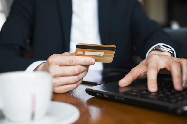 Close-up van mannelijke handen met behulp van een gouden kaart tijdens het werken op een laptop met een andere hand.