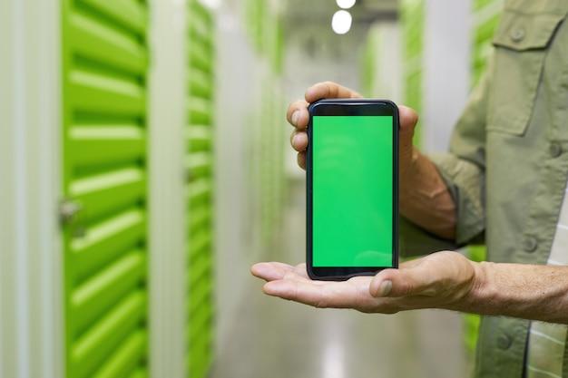 Close-up van mannelijke handen met smartphone met groen scherm tegen zelf opslag faciliteit oppervlak, kopieer ruimte