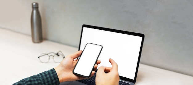 Close-up van mannelijke handen met smartphone naast laptop met mockup op achtergrond van bureau met thermo-waterfles en ronde bril.