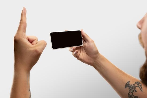 Close-up van mannelijke handen met telefoon met leeg scherm tijdens het online kijken naar populaire sportwedstrijden en kampioenschappen. copyspace voor advertentie. nieuwe regels voor veiligheid. apparaten, gadgets, technologieën concept.