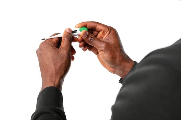 Close-up van mannelijke handen met thermometer die temperatuur opneemt