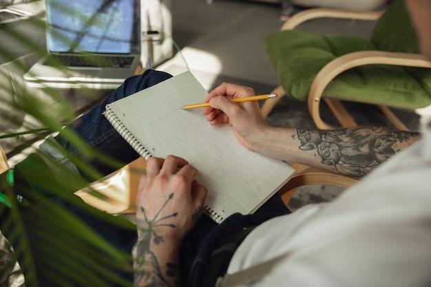Close up van mannelijke handen schrijven op een leeg papier op tafel thuis.