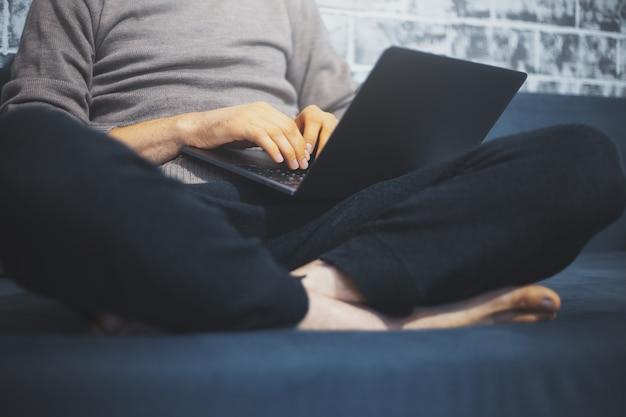 Close-up van mannelijke handen typen op toetsenbord van laptop op zijn benen, man zittend op de bank thuis.