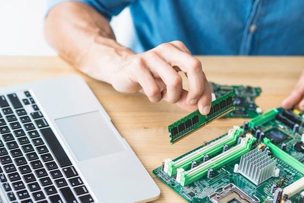 Close-up van mannelijke it-ingenieur die ram op motherboard assembleert