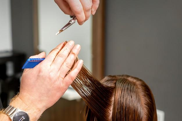 Close up van mannelijke kapper handen snijdt vrouwelijk haar in een kapsalon. selectieve aandacht