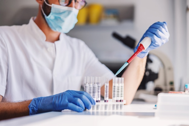 Close-up van mannelijke laboratoriumassistent met rubberhandschoenen en gezichtsmaskerzitting in laboratorium en het testen van bloed