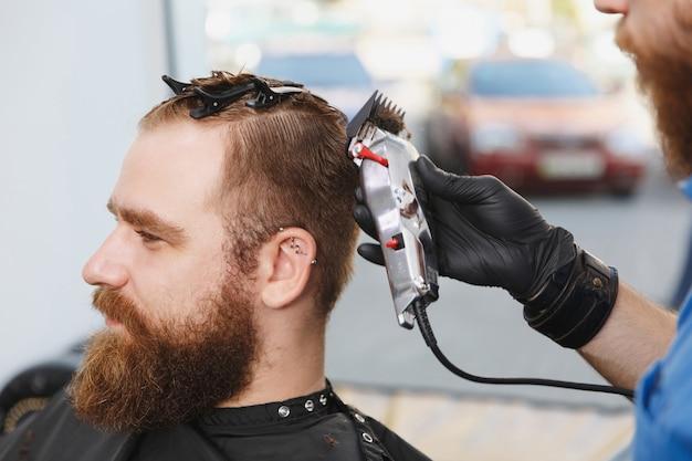 Close up van mannelijke professionele kapper die klant bedient door clipper
