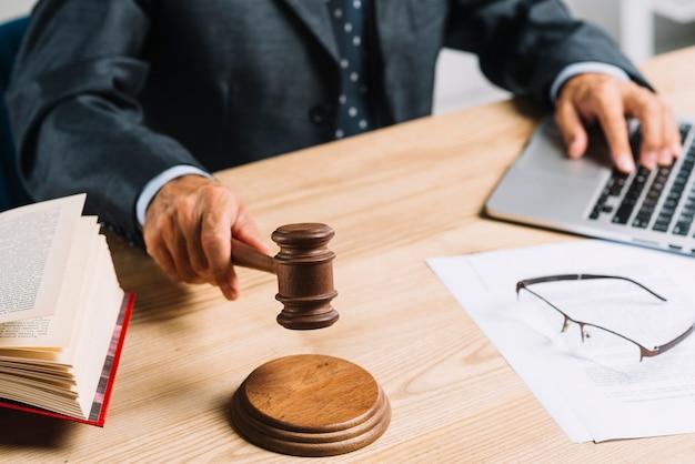 Close-up van mannelijke rechter die oordeel geven door hamer bij bureau in de rechtszaal te raken