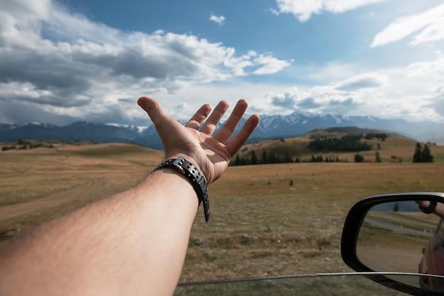 Close up van mannelijke reiziger hand in auto ontspannen en genieten van road trip in altai gebergte zomer vac...