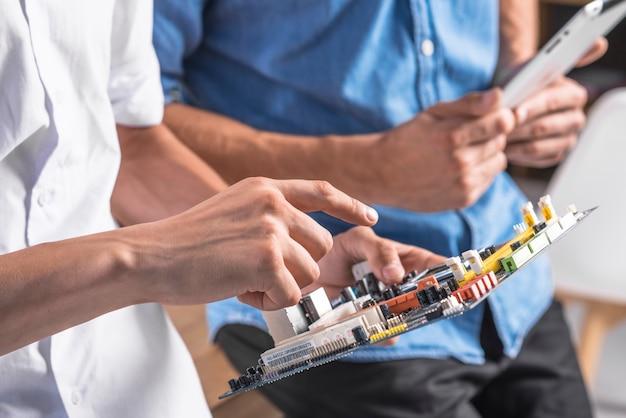 Close-up van mannelijke technicus die op motherboard richten