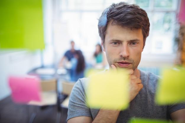 Close-up van mannelijke uitvoerende lezen sticky notes