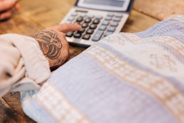 Close-up van mannelijke verkoper die calculator gebruiken dichtbij de textielstof op houten lijst in winkel