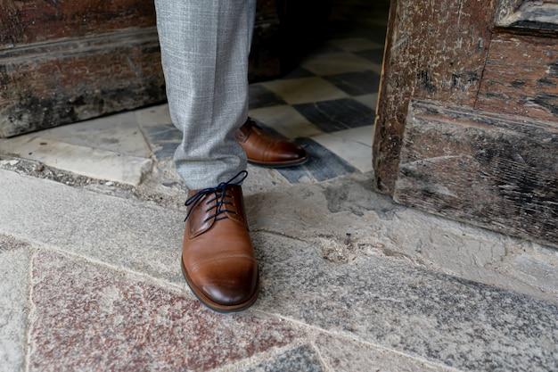 Close-up van mannenbenen in stijlvolle bruine schoenen.