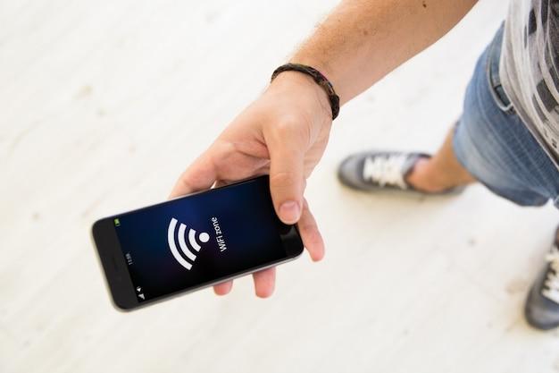 Close-up van mannenhand met behulp van smartphone wifi-zone