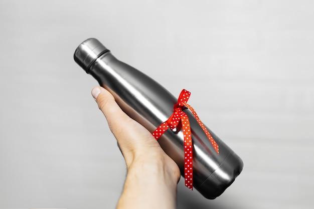 Close-up van mannenhand met een eco water thermo fles staal met rood lint