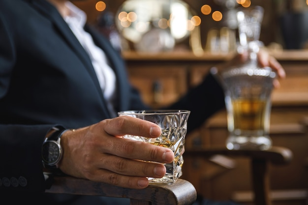 Close-up van mannenhand met een glas dure whisky