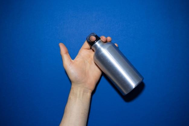 Close-up van mannenhand met herbruikbare aluminium thermo waterfles geïsoleerd op fantoomblauw van kleur.