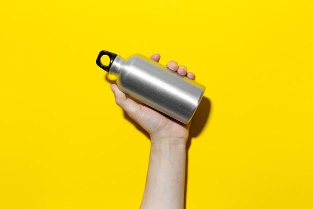 Close-up van mannenhand met herbruikbare aluminium thermo waterfles op achtergrond van gele kleur.