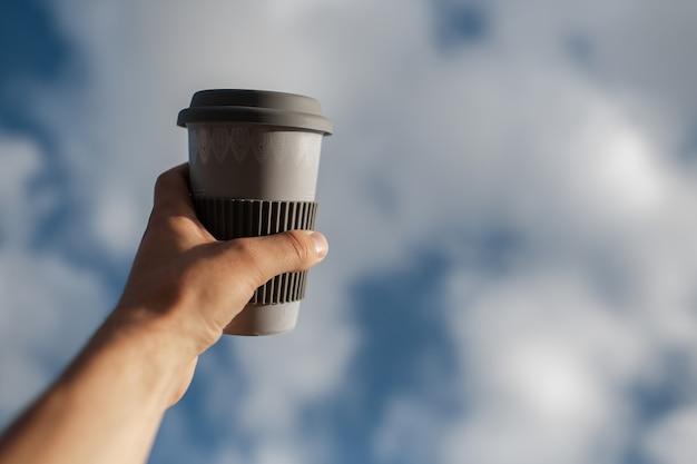 Close-up van mannenhand met koffiemok op achtergrond van zonnige hemel.