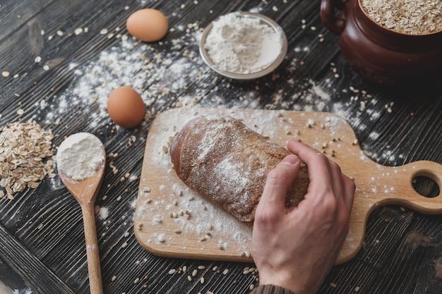 Close-up van mannenhanden op zwart brood met bloempoeder. bakken en patisserie concept. Premium Foto