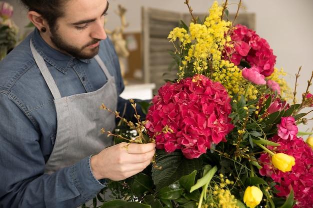 Close-up van mannetje dat de bloemen in het boeket schikt