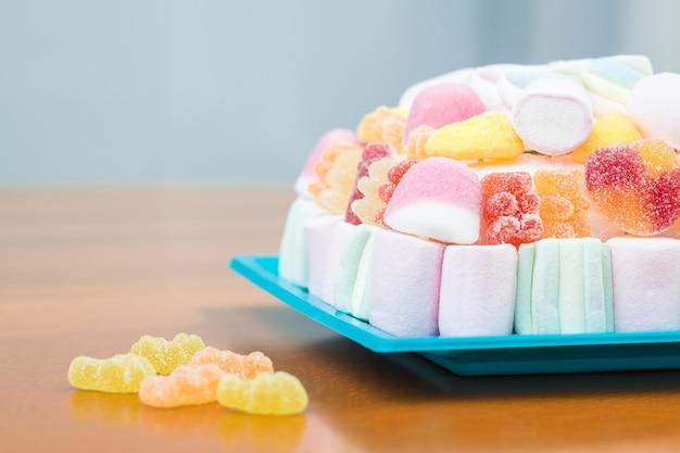 Close-up van marshmallows en jelly beans cake over blauw bord voor een kinderfeestje, in zachte pasteltinten