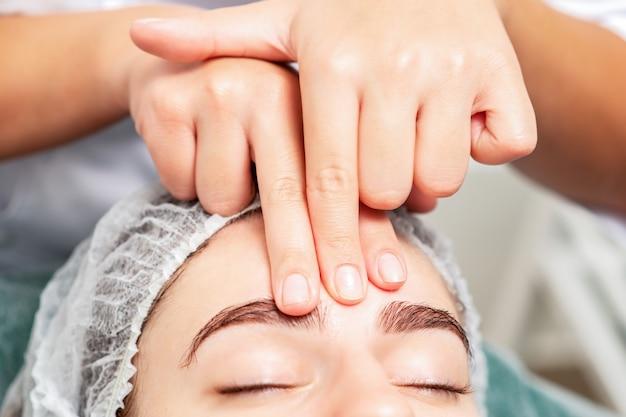 Close-up van massage van voorhoofd van vrouw door vingers van massagetherapeut bij schoonheidssalon.