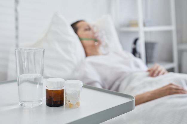 Close-up van medicijnen en glas water op tafel met zieke patiënt op de achtergrond