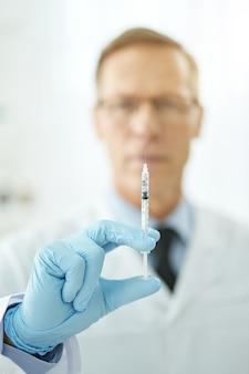 Close up van medische werker in steriele handschoenen geneesmiddel voorbereiden voor injectie