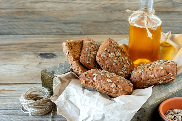 Close-up van meergranen of volkoren broodjes met oliefles in een doek bekleed met houten kist.