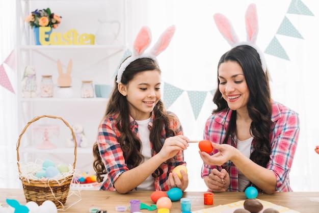Close-up van meisje en moeder kleurende eieren voor pasen thuis