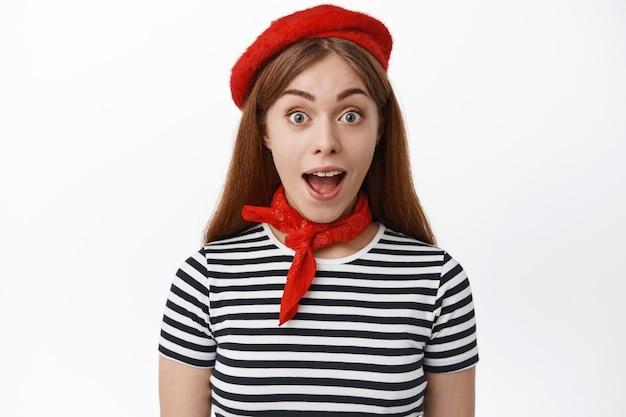 Close-up van meisje in franse outfit ziet er opgewonden en geamuseerd uit, bekijkt geweldig groot nieuws, staande tegen een witte muur