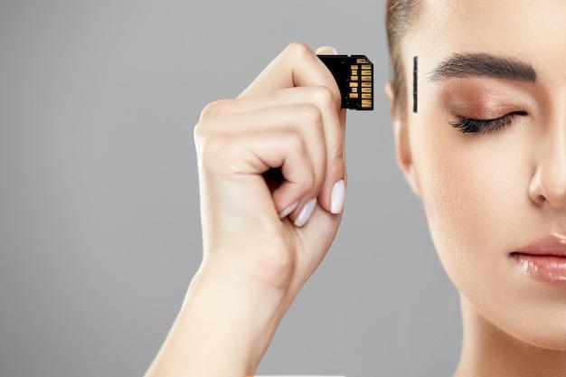 Close-up van meisje met geheugenkaart in de buurt van tempel om deze in haar hoofd, nieuwe technologiewereld, techno-tijdperk en mensenleven te steken