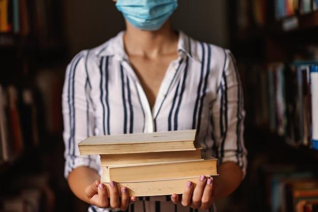 Close-up van meisje met gezichtsmasker dat zich in bibliotheek bevindt en boeken houdt. studeren tijdens pandemisch concept.