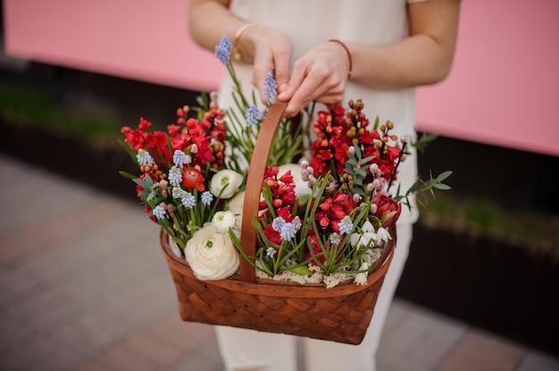 Close-up van meisje met mand met rode en blauwe bloemen