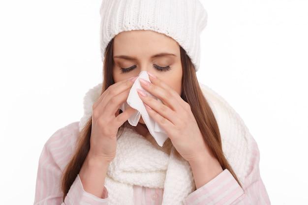 Close-up van meisje met wollen muts blaast haar neus