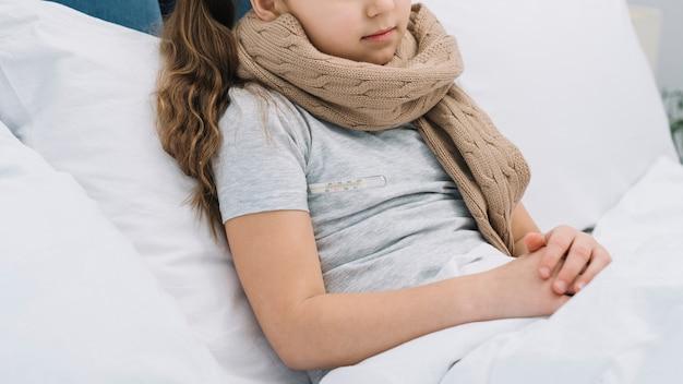 Close-up van meisje met wollen sjaal rond haar hals liggend op bed