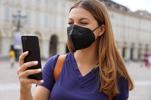 Close up van meisje met zwart beschermend masker ffp2 kn95 met behulp van slimme telefoon met stedelijke achtergrond