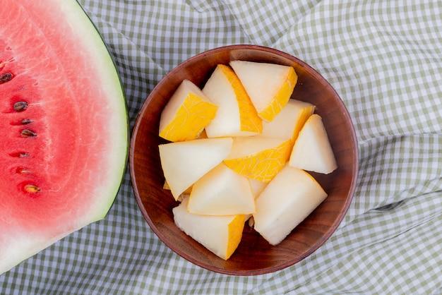 Close-up van meloen segmenten in kom met watermeloen half op plaid doek achtergrond